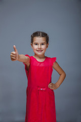 Teen girl child in red dress showing thumbs up sign yes on a gra