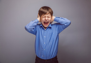 teenager boy covering his ears screaming hands on a gray backgro