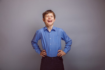 teenager boy laughing on gray background