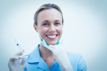 Smiling female dentist holding injection