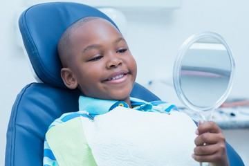 Boy looking at mirror in the dentists chair