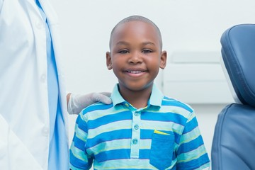 Smiling boy standing by cropped dentist