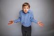 teenager boy shrugs at a loss - 75947783