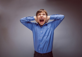 teenager boy shouts shut ears opened his mouth on a gray bac