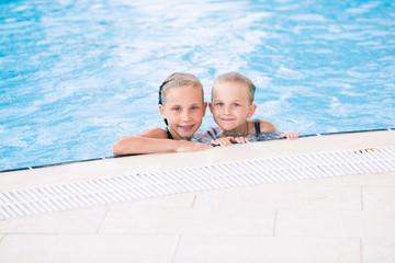 Two cute little girls in swimming pool