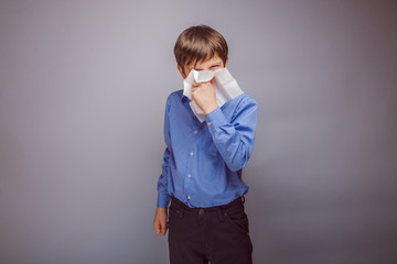 teenager boy sick sneezing into a handkerchief on gray backgro