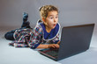the girl child is playing in a laptop surprised on gray backgr