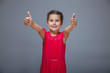 the girl child is showing thumbs up gesture yes on a gray backgr