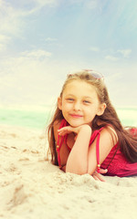 Cute little girl lying on the sand near the sea