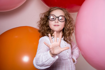 Portrait of a teenage schoolgirl showing five fingers on a backg