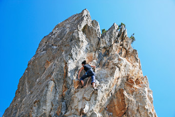 Young woman climbing vertical natural rocky wall