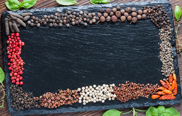 Assorted dry pepper on a background of black slate board