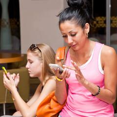 Две девушки с телефонами в руках