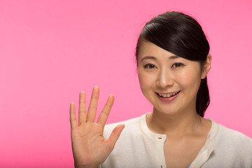Young Asian woman waving hand hello