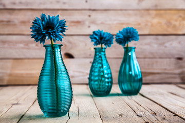blue gerbera flower in a vase on wooden background