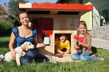 Happy kids painting the doghouse