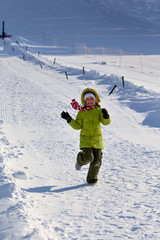 Девочка в зеленом бежит по снегу