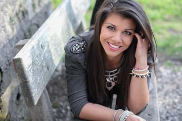 Pretty woman laying on a bench smiling at camaera