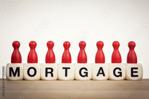 Mortgage concept: Red pawns on the word mortgage spelled  - 75956960