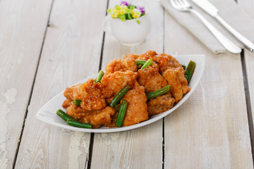 pieces of chicken in batter with spicy sauce and green beans