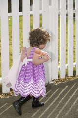 little girl in front of white fence with her doll