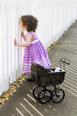 little girl with stroller looking through fence
