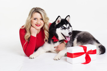 Girl wearing dress with gifts and her husky dog