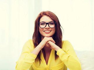 smiling teenage girl in eyeglasses at home