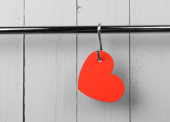 Red heart on stainless steel kitchen wall rack. Copy space.