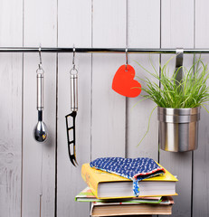 Red heart and kitchen cooking utensil on stainless steel rack.