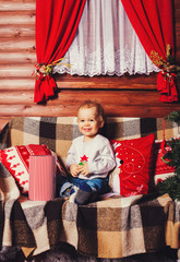 Happy kid sitting and smiling near Christmas tree