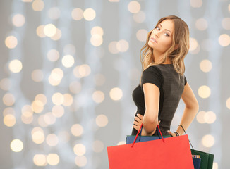 young happy woman with shopping bags over lights