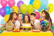 canvas print picture - Kids celebrating birthday party and blowing candles on cake