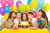 Kids celebrating birthday party and blowing candles on cake - 75960735