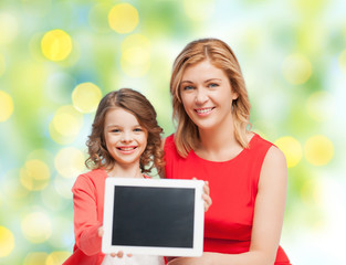 mother and daughter with tablet pc over green