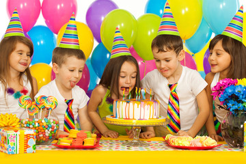 Group of joyful little kids with cake at birthday party