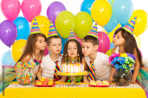 Fototapeta Kids celebrating birthday party and blowing candles on cake