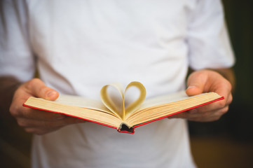 Open book with heart-shape sheets  in the male hands