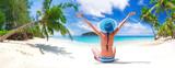 Woman in hat enjoying sun holidays on the tropical beach