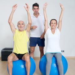 Physiotherapeut zeigt Senioren eine Übung