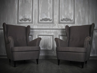 Two classic armchairs against a gray wall and floor