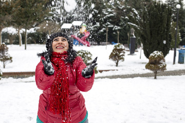 Happy young Turkish woman plays with a snow outdoor