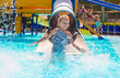 Little girl on water slide at aquapark during summer holiday - 75964124