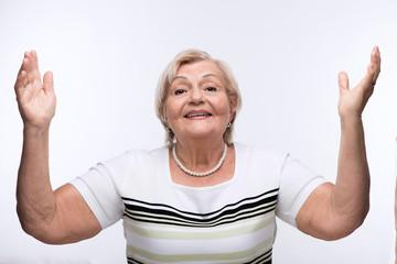Elderly lady raising hands