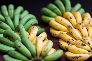Banana in market.  Bunches of ripe yellow and unripe green banan