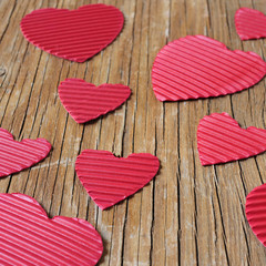 red hearts on a rustic wooden surface