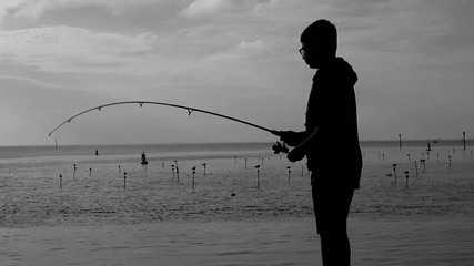 silhouette of boy tugging at fishing pole