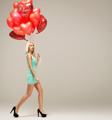 Attractive young blond woman model with balloons in motion isola
