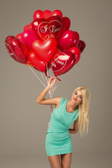 Blond woman model with red balloons heart