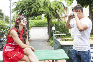 young adult takes pictures of his girlfriend in fifties style